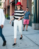 Kendall Jenner out about wearing a red hat, white pants, and a striped shirt in New York City