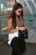 Selena Gomez is busy on her phone as she is spotted departing Toronto International Airport.